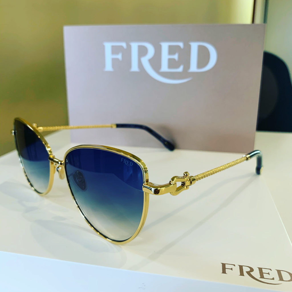 Fred glasses sitting on a table. Gold frames, blue lenses.